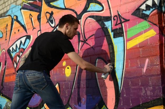 그의 목에 배낭과 가스 마스크와 젊은 낙서 예술가 화려한 낙서 페인트 프리미엄 사진