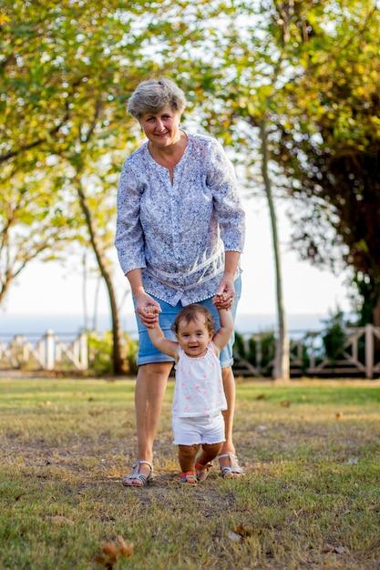 若い祖母と祖父が緑豊かな公園で彼女の孫娘と散歩に Premium写真