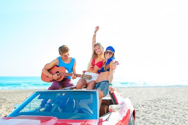 Young group having fun on beach playing guitar Premium Photo