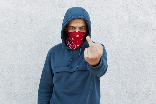 Young guy in bandana mask calls for stopping police brutality, showing middle finger Free Photo