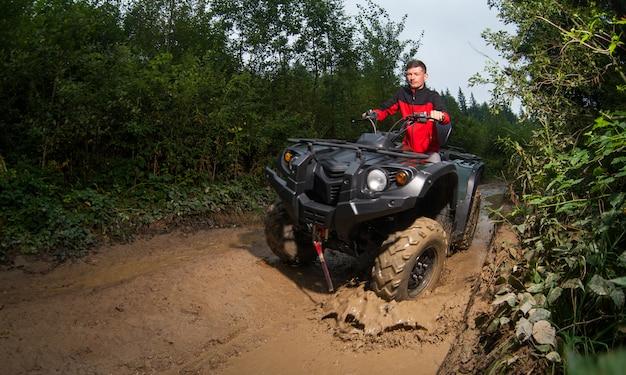 Young guy driving four-wheeler atv through mud Premium Photo