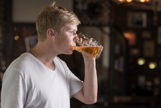 Young guy enjoying beer in pub Free Photo