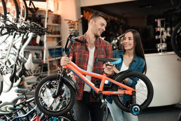 A young guy and a girl are choosing a children's bicycle. Premium Photo