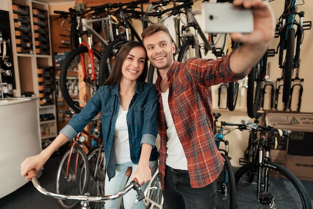 A young guy and a girl make a selfie at a bike store Premium Photo