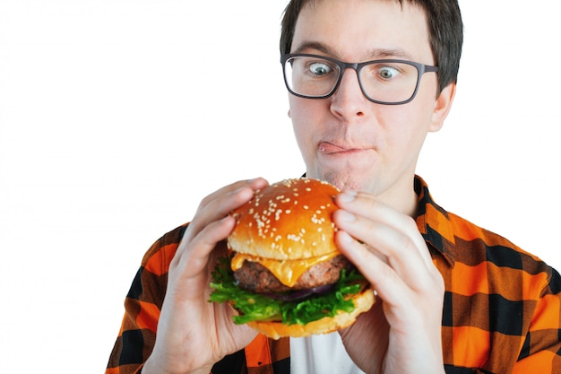 A young guy holding a fresh burger. Premium Photo