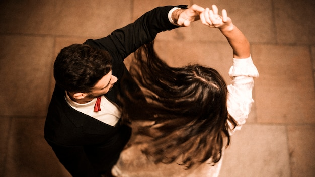 Young guy holding hand of whirling elegant lady Premium Photo