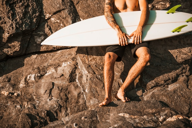 Young guy holding surf board near stones Free Photo