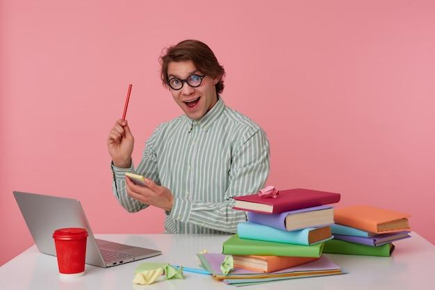眼鏡をかけた若い男がテーブルのそばに座ってラップトップで作業し、カメラを見て、鉛筆とステッカーを手に持って、ピンクの背景の上に隔離された素晴らしいアイデアを持っています。 無料写真
