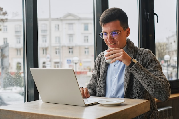 Young guy is freelancer in cafe working behind a laptop. man drinking coffee. Premium Photo