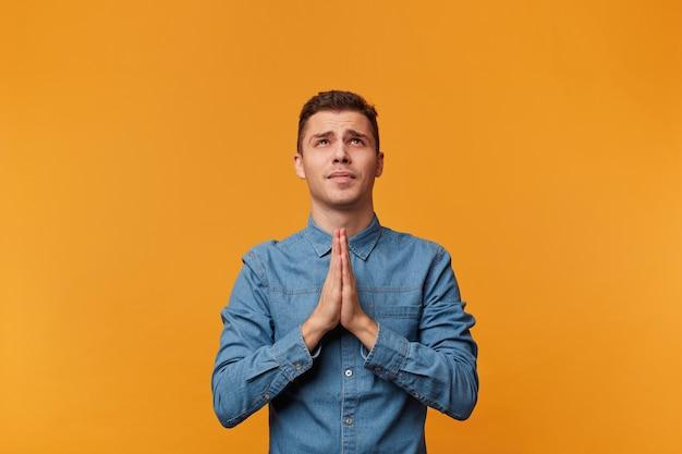 若い男は希望を持って見上げ、手のひらを祈りのジェスチャーで折りたたんで、より高い力からの助けを求めます 無料写真