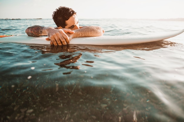 Young guy lying on surf board in water Free Photo