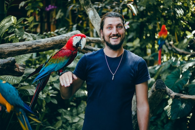 Young guy posing in a zoo with a parrot in his hand, a bearded man and a bird Free Photo