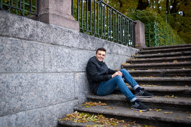 A young guy sitting on the stairs. Premium Photo
