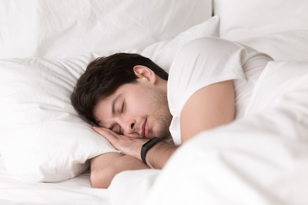 Smartwatch 또는 수면 추적기를 입고 침대에서 자고있는 젊은 남자 무료 사진