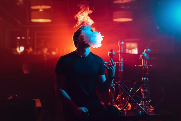 Young guy smokes a shisha and lets out a cloud of smoke Premium Photo
