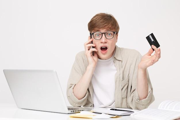 電話で銀行のマネージャーと話している若い男 無料写真