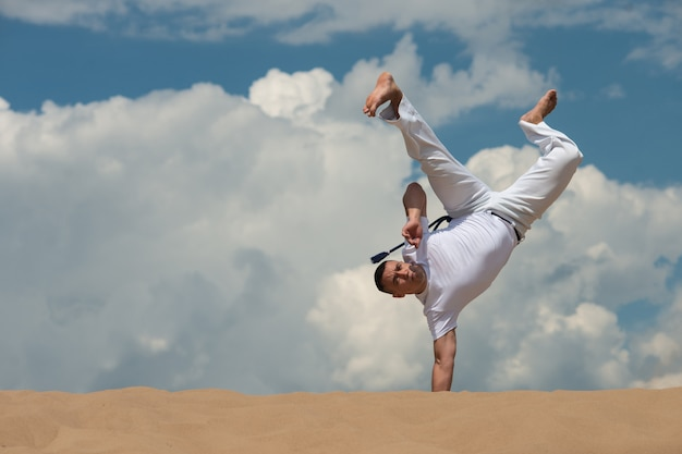 A young guy trains capoeira against the sky. a man performs an acrobatic trick Premium Photo