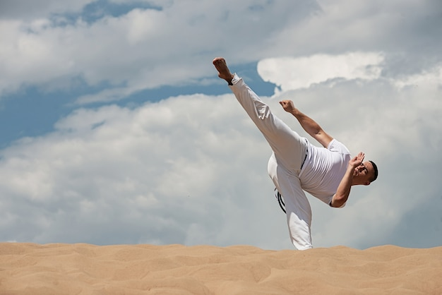 Young guy trains capoeira on sky backround. a men performs martial the kick Premium Photo