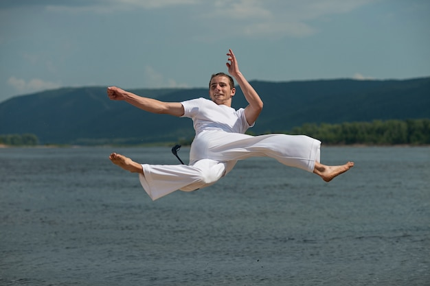 Young guy trains capoeira in the sky Premium Photo