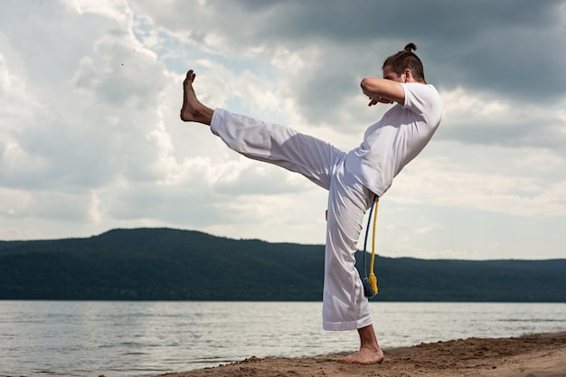 Young guy trains capoeira Premium Photo
