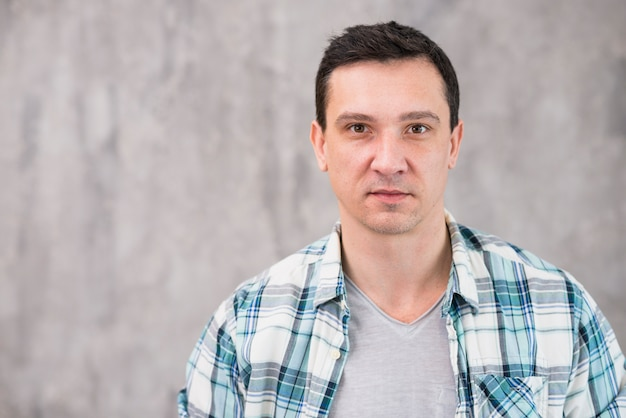 Young guy with back hair in flannel shirt looking at camera Free Photo