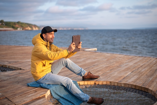 Young guy in a yellow windbreaker, black cap sitting on a wooden pier, takes a photo of sunrise on the tablet Premium Photo