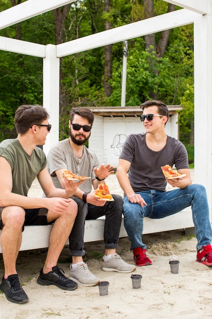Young guys talking while holding pizza on rest Free Photo
