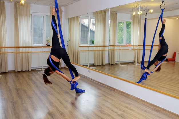 Young gymnast woman doing gymnastics on rope in aerial fitness gym Premium Photo