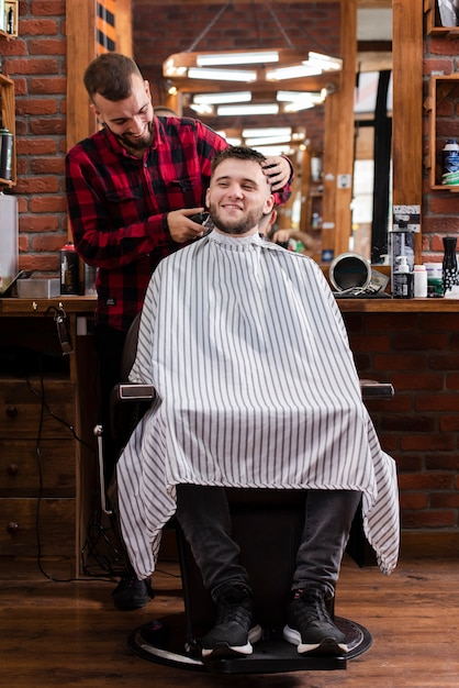 Young hairdresser and customer smiling Free Photo