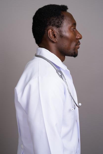 灰色の背景の若いハンサムなアフリカ人医師 Premium写真