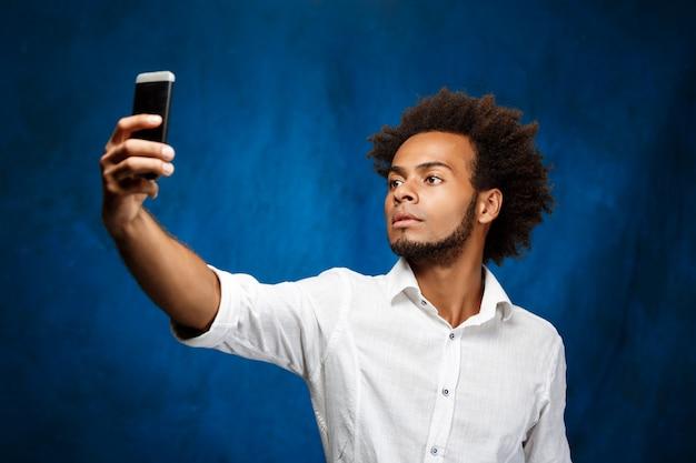 水色の壁でselfieを作る若いハンサムなアフリカ人。 無料写真
