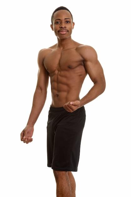 Молодой красивый африканский мужчина без рубашки сгибает левую руку Premium Фотографии