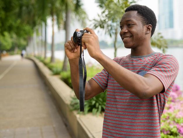 Молодой красивый африканский мужчина фотографирует с камерой в парке Premium Фотографии
