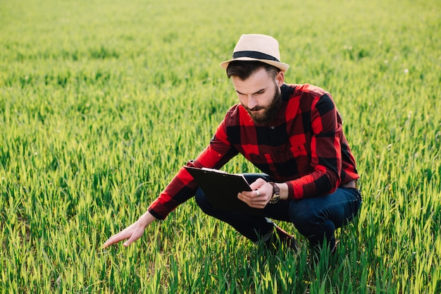 Young handsome bearded farmer with folder analyzes the crop in wheat field in early summer Premium Photo