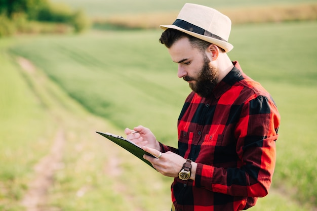 Young handsome bearded farmer with folder standing in green wheat field in early summer Premium Photo