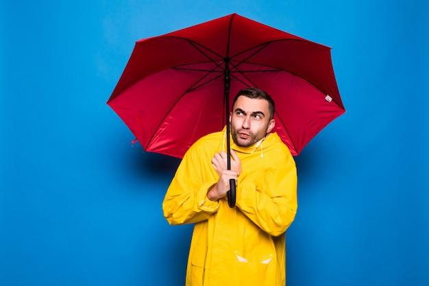 Молодой красивый бородатый мужчина в желтом плаще с красным зонтиком от дождя простужается изолированно на синем фоне Premium Фотографии