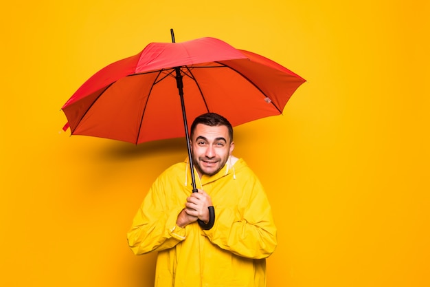 Молодой красивый бородатый мужчина в желтом плаще с красным зонтиком от дождя простужается изолированно на оранжевом фоне Premium Фотографии