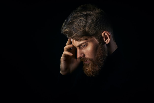 Young handsome bearded man with  beard and stylish haircut think Premium Photo