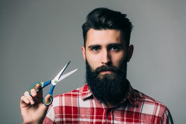 Молодой красивый бородатый мужчина с длинными усами и волосами брюнетки держит парикмахерские или парикмахерские ножницы с эмоциональным лицом на серой стене Бесплатные Фотографии