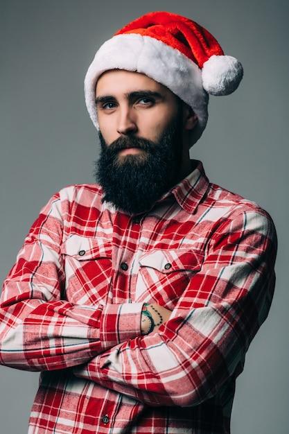 灰色の壁に赤いクリスマスの帽子を持つ若いハンサムなひげを生やした男 無料写真