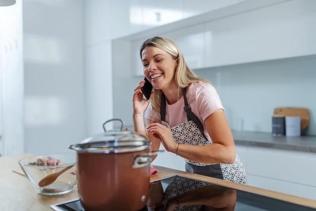 Молодая красивая блондинка ленивая домохозяйка стоит на кухне, разговаривает по телефону, пока горшок с обедом стоит на плите. Premium Фотографии