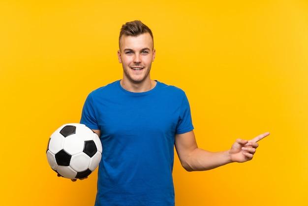 驚いたと側に指を指している分離の黄色の壁にサッカーボールを保持している若いハンサムな金髪男 Premium写真