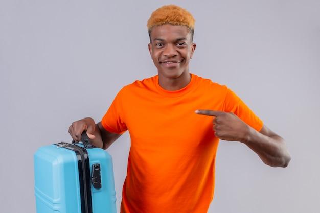 それを指で指している旅行スーツケースを保持しているオレンジ色のtシャツを着ている若いハンサムな男の子 無料写真