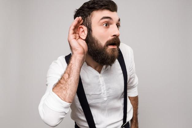 若いハンサムな黒髪の男が白で盗聴します。 無料写真