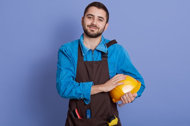 Young handsome builder holding yellow helmet in hands, does repairing, wears casual brown apron Premium Photo
