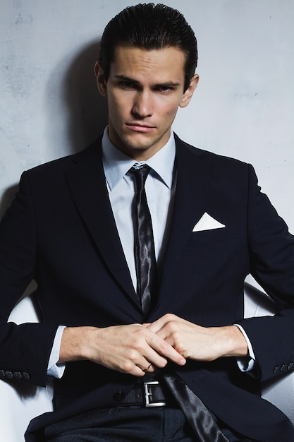 Young handsome business man in black suit sits in chair on grey wall Premium Photo