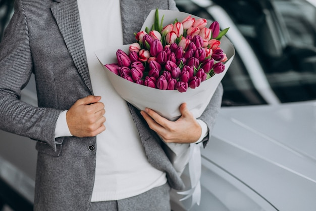 Young handsome business man delivering bouquet of beautiful flowers Free Photo