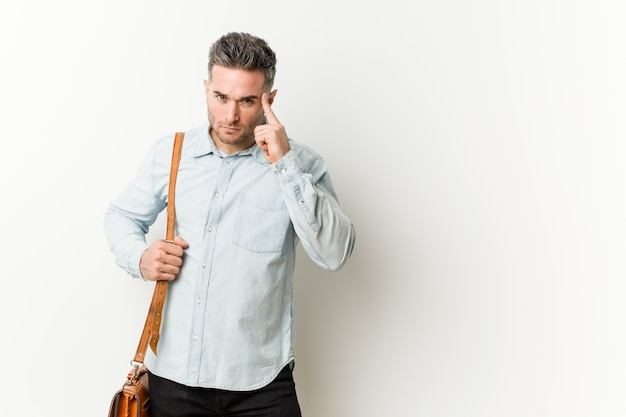 Young handsome business man pointing temple with finger, thinking, focused on a task. Premium Photo
