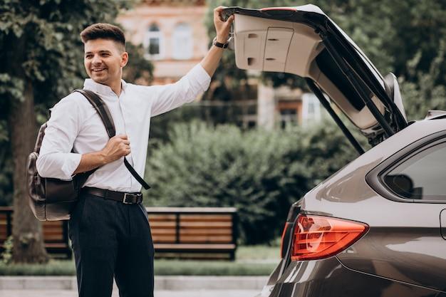 旅行バッグが付いている車で立っている若いハンサムなビジネス男 無料写真