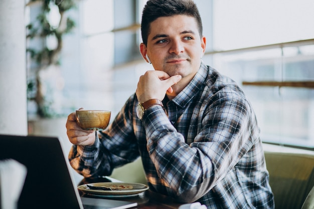 Young handsome business man using laptop in a cafe Free Photo